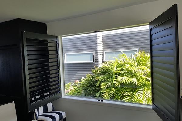 Bi-fold shutters opening onto ferns outside