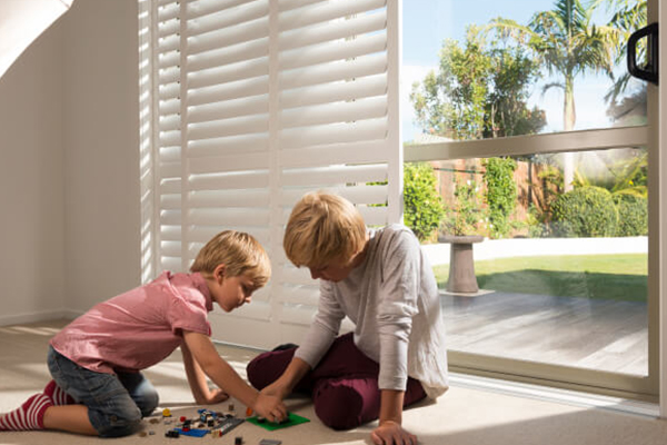 Kids playing with shutters behind them