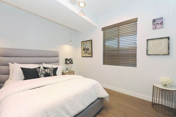 Small venetian blinds on window above modern white bed